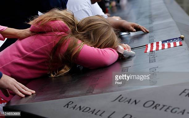 Mourners touch the names of lost loved ones during tenth anniversary ceremonies of the September 11 2001 terrorist attacks at the World Trade Center...