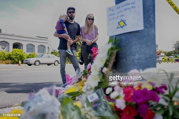 Mourners Troy and Katie McKinney and their son Wynn look over a make-shift memorial across the street from the Chabad of Poway Synagogue on Sunday,...