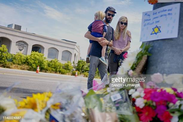 Mourners Troy and Katie McKinney and their son Wynn look over a makeshift memorial across the street from the Chabad of Poway Synagogue on Sunday...