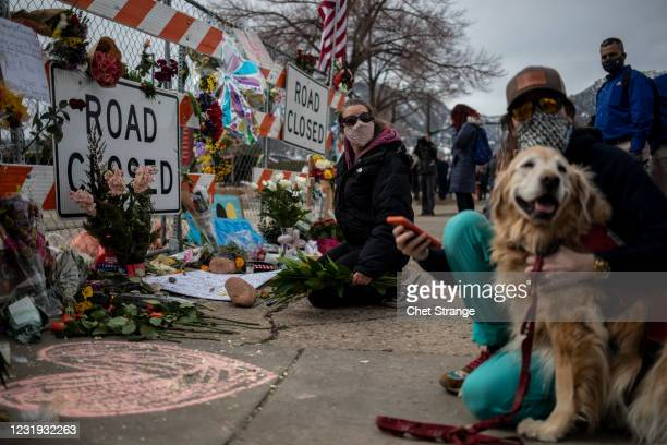 Mourners visit a makeshift memorial set up outside the site of a shooting at a King Soopers grocery store on March 25, 2021 in Boulder, Colorado. The...