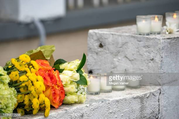 Mourners visit and leave flowers at the site of two shootings at spas across the street from one another, in memorial for the lives lost, on March...