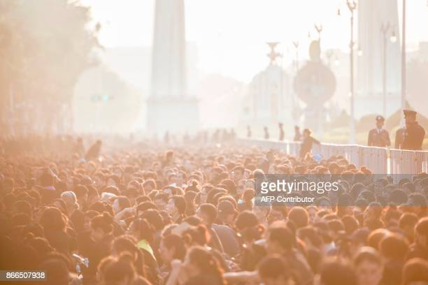 Mourners wait for the funeral procession for the late Thai King Bhumibol Adulyadej to take place outside the Grand Palace in Bangkok early on October...