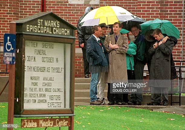 Mourners wait in the rain outside of St Mark's Espiscopal Church 16 October in Casper Wyoming for the funeral services of Matthew Shepard a gay...