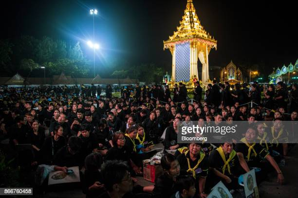 Mourners watch a large screen unseen during the cremation ceremony of the late King Bhumibol Adulyadej at the Royal Plaza in Bangkok Thailand on...