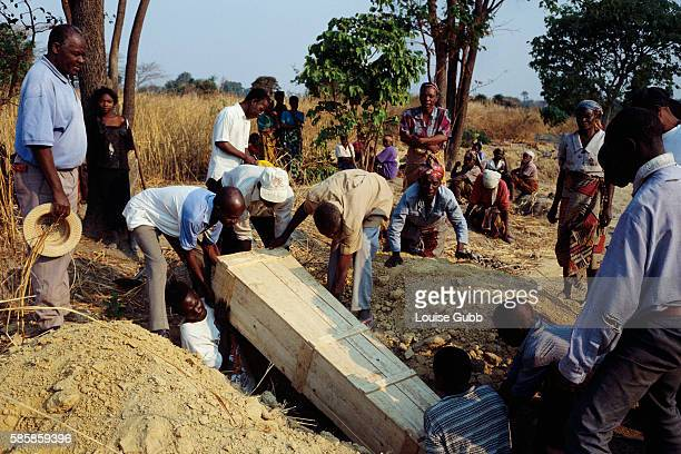 Mourners watch as a coffin is lowered into a grave the deceased a victim of AIDS and mother of four young children now orphans Seventy percent of the...