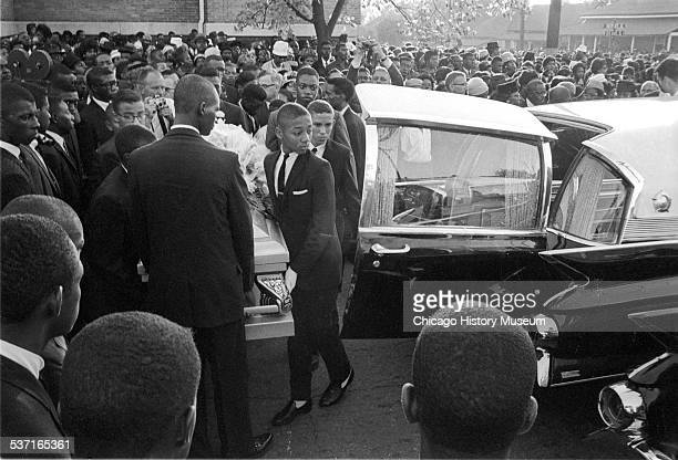 Mourners watch as group of young pallbearers carry a casket towards a hearse at a funeral for victims of the 16th Street Baptist Church bombing in...
