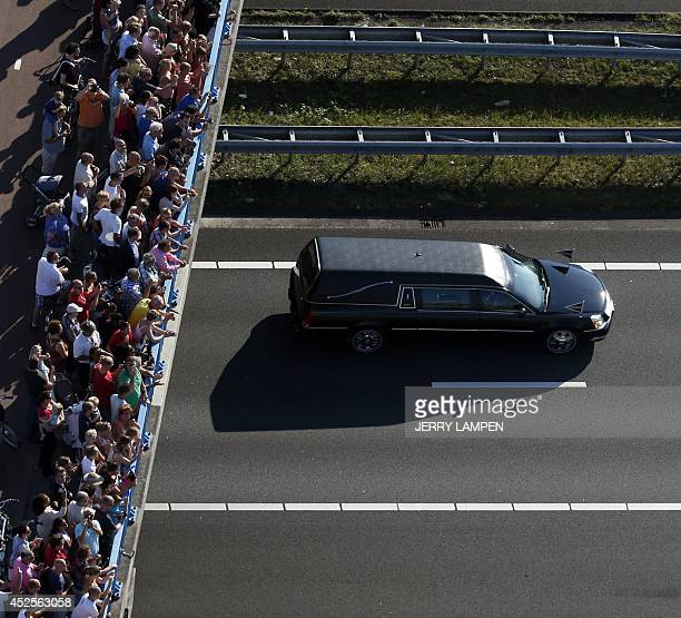 Mourners watch from a bridge a convoy of hearses carrying coffins containing the remains of victims of the downed Malaysia Airlines flight MH17...