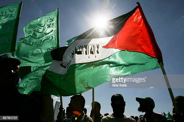 Mourners wave Palestinian and Hamas flags while they wait the funeral of 15 Palestinian bomb victims in the Alshuhada cemetery September 24 2005 in...