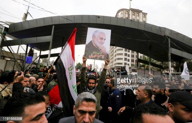 Mourners wave the national flag and the Hashed al-Shaabi flag as they carry the portrait Iranian military commander Qasem Soleimani during a funeral...