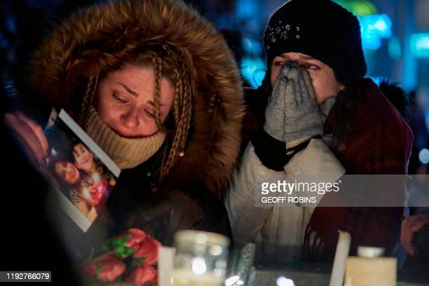 Mourners weep during a vigil for the victims of Ukrainian Airlines flight 752 which crashed in Iran during a vigil at Mel Lastman Square in Toronto,...