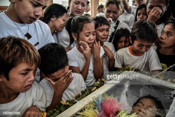 Mourners weep over the coffin of 13yearold Aldrin Pineda who was shot to death by a police officer during his funeral in Manila Philippines March 14...