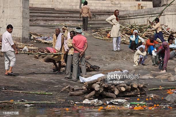 Mourners with bodies for Hindu cremation at Harishchandra Ghat crematorium in Holy City of Varanasi Benares India