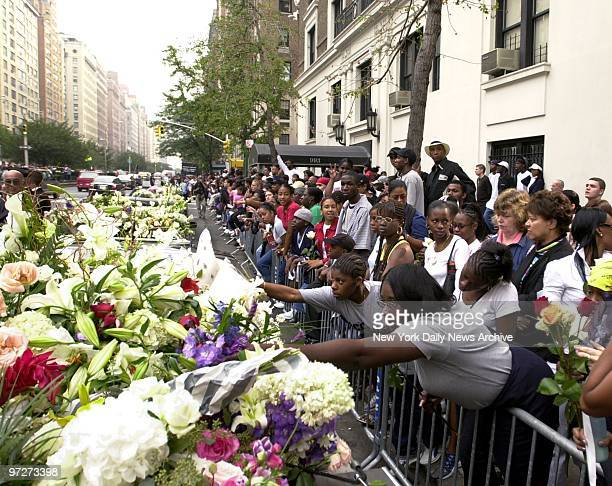 Mourning fans add their tributes to banks of flowers as the casket of RB star Aaliyah is borne from the Frank E Campbell Funeral Chapel on 81st St to...