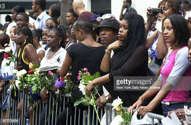 Mourning fans line the streets outside St Ignatius Loyola Roman Catholic Church at 84th St and Park Ave as pallbearers carry the casket of RB star...