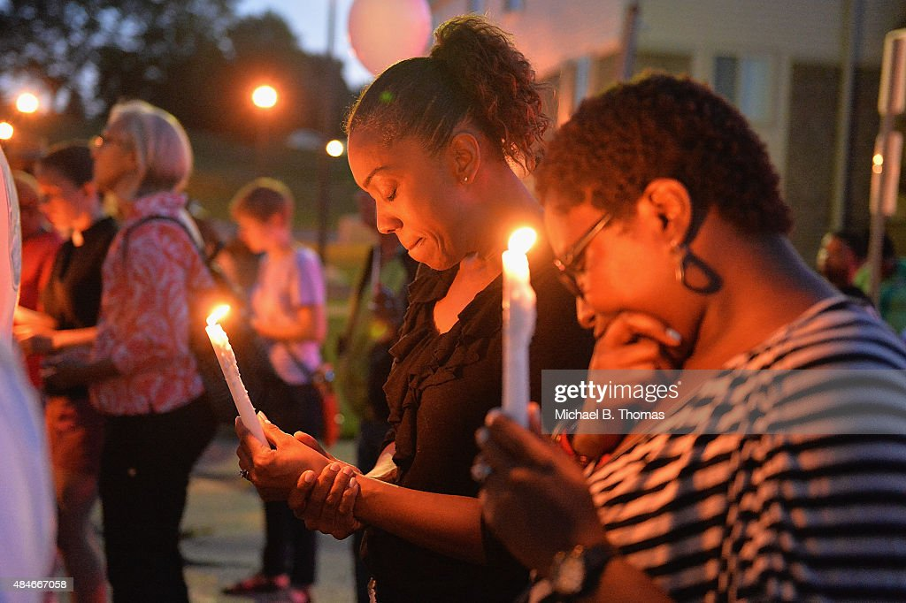 Mourning participants pause in a moment of prayer at the Michael Brown Jr. memorial during a candlelight vigil held in honor of Jamyla Bolden on August 20, 2015 in Ferguson, Missouri. Jamyla Bolden, 9, was allegedly struck by a stray bullet from a drive-by shooting and killed while doing her homework at her home in Ferguson on August 18th.