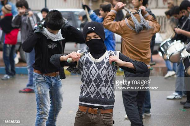 Mourning shi'a muslim boys, using iron chains for self-flagellation, a common practice on the Day of Ashura, on which shi'a muslims commemorate the...