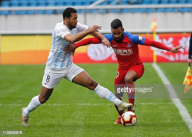 Mousa Dembele of Guangzhou RF competes for the ball with Fernandinho of Chongqing Lifan during their Chinese Super League football match in Chongqing...