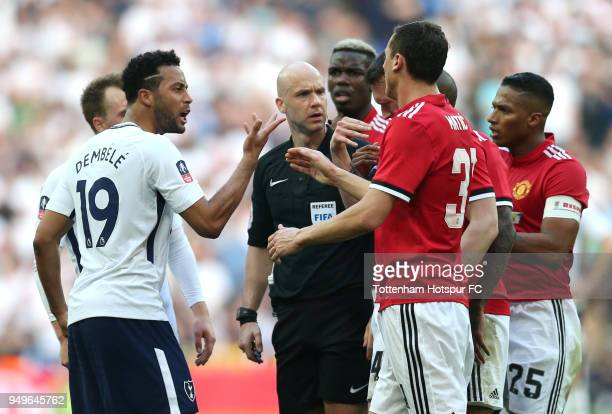 Mousa Dembele of Tottenham Hotspur confronts Phil Jones of Manchester United and Nemanja Matic of Manchester United infront of referee Anthony Taylor...