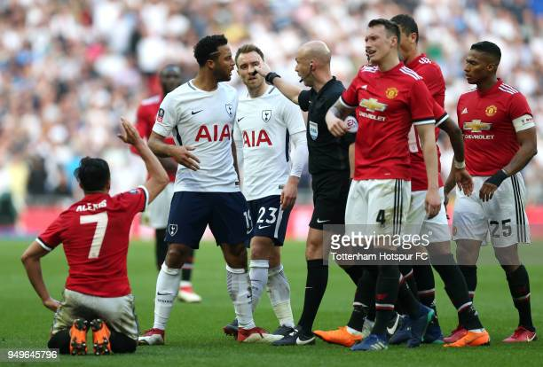 Mousa Dembele of Tottenham Hotspur confronts Phil Jones of Manchester United infront of referee Anthony Taylorafter he fouled Alexis Sanchez of...