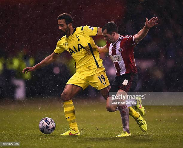Mousa Dembele of Tottenham Hotspur is challenged by Michael Doyle of Sheffield United during the Capital One Cup SemiFinal Second Leg match between...