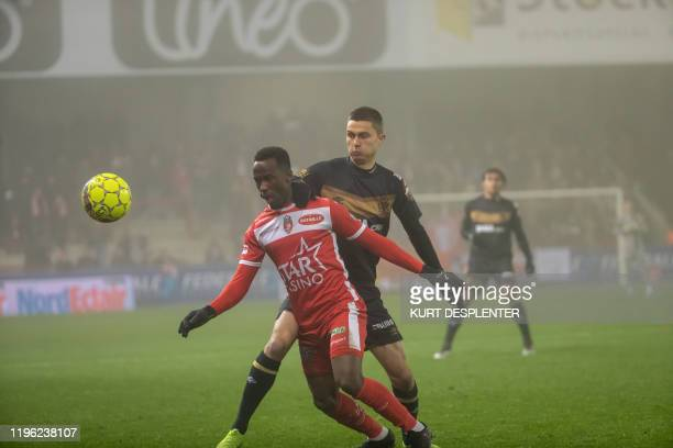 Mouscron's Fabrice Olinga and STVV's Wolke Janssens fight for the ball during a soccer match between RE Mouscron and STVV SintTruiden Saturday 25...