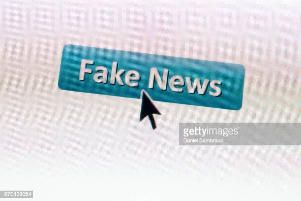 Mouse arrow clicking on a FAKE NEWS button on computer screen
