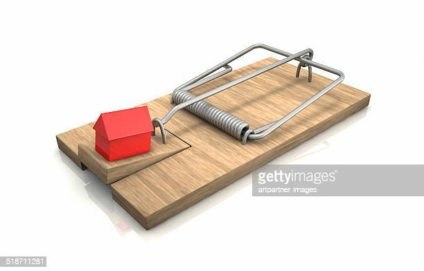 Mouse trap with a red house as bait on white