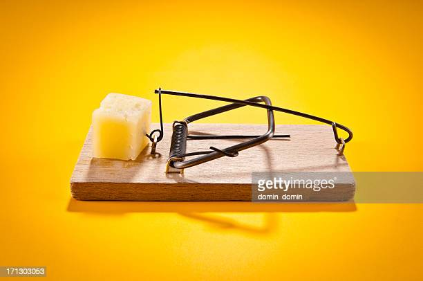 Mousetrap with hard cheese isolated on yellow, side view