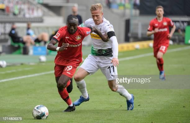 Moussa Diaby of Bayer 04 Leverkusen is challenged by Oscar Wendt of Borussia Moenchengladbach during the Bundesliga match between Borussia...