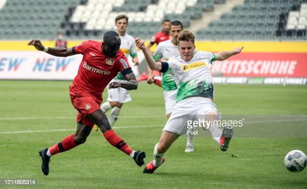 Moussa Diaby of Bayer 04 Leverkusen shoots as Nico Elvedi attempts to block during the Bundesliga match between Borussia Moenchengladbach and Bayer...