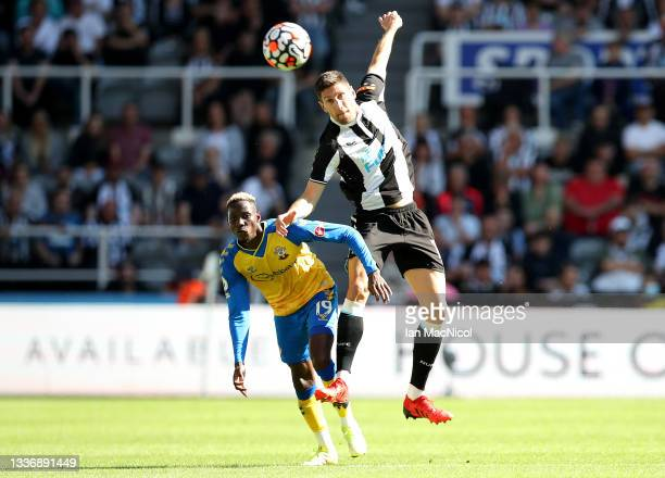 Moussa Djenepo of Southampton battles for possession with Federico Fernandez of Newcastle United during the Premier League match between Newcastle...