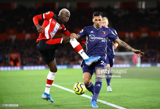 Moussa Djenepo of Southampton crosses the ball under pressure from Jose Holebas of Watford during the Premier League match between Southampton FC and...