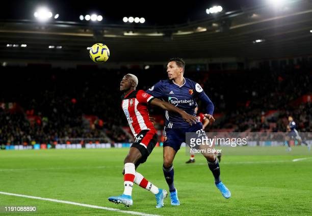 Moussa Djenepo of Southampton is challenged by Jose Holebas of Watford during the Premier League match between Southampton FC and Watford FC at St...