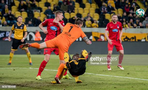 Moussa Kone of Dresden is challenged by goalkeeper Kevin Mueller of Heidenheim during the Second Bundesliga match between SG Dynamo Dresden and 1. FC...