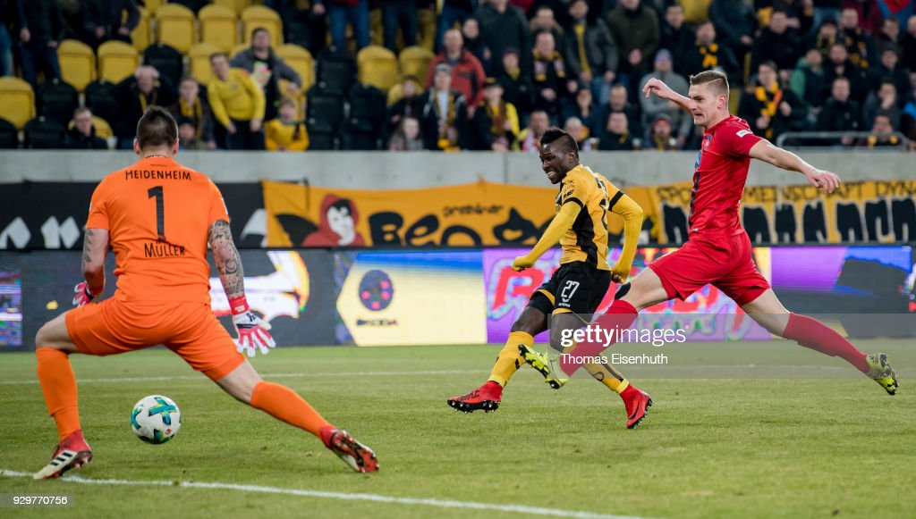 Moussa Kone (C) of Dresden scores his team's second goal past goalkeeper Kevin Mueller (L) and Kevin Kraus of Heidenheim during the Second Bundesliga match between SG Dynamo Dresden and 1. FC Heidenheim 1846 at DDV-Stadion on March 9, 2018 in Dresden, Germany.