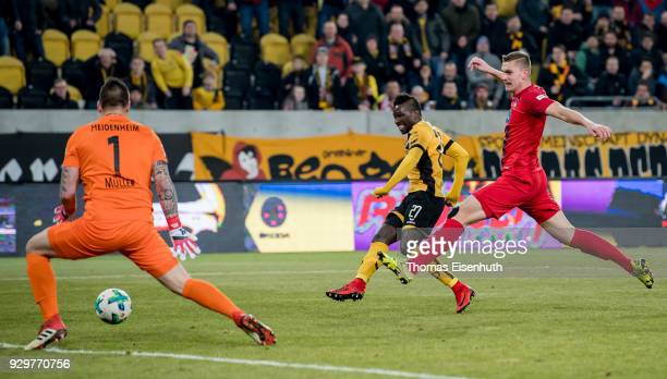 Moussa Kone of Dresden scores his team's second goal past goalkeeper Kevin Mueller and Kevin Kraus of Heidenheim during the Second Bundesliga match...