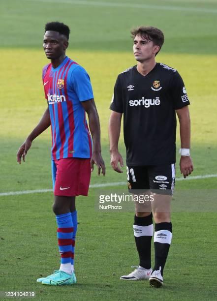 Moussa Ndiaye and Ivan De la Pena Jr, son of former player Ivan De la Pena, during the friendly match between FC Barcelona and Club Gimnastic de...