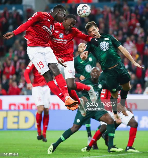 Moussa Niakhate and Jean-Philippe Mateta of Mainz jump for a header with Ignacio Camacho of Wolfsburg during the Bundesliga match between 1. FSV...
