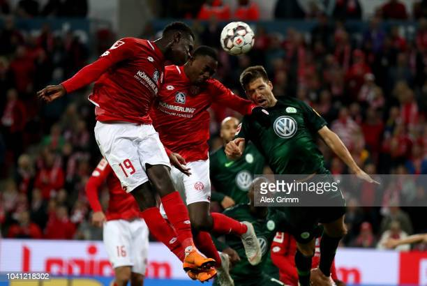 Moussa Niakhate, Jean Philippe Mateta of Mainz and Ignacio Camacho of Wolfsburg head for the ball during the Bundesliga match between 1. FSV Mainz 05...