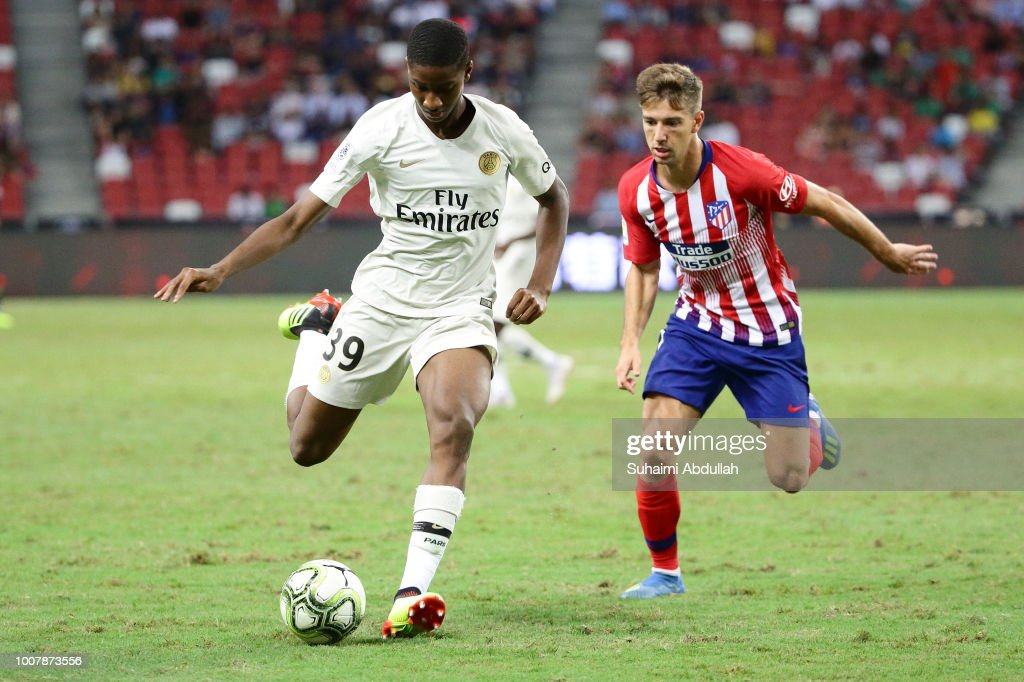 Moussa Sissako of Paris Saint Germain dribbles past Luciano Vietto of Atletico Madrid during the International Champions Cup 2018 match between Atletico Madrid and Paris Saint Germain at the National Stadium on July 30, 2018 in Singapore.