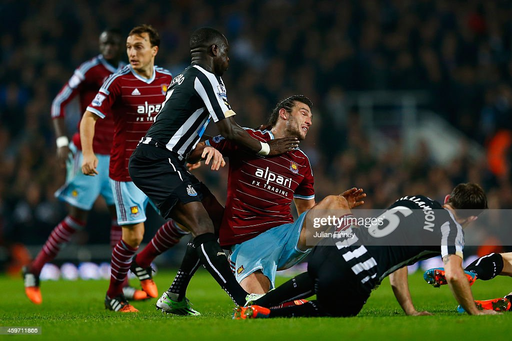 Moussa Sissoko of Newcastle United challneges Andy Carroll of West Ham and is sent off as a result with a second yellow card during the Barclays Premier League match between West Ham United and Newcastle United at Boleyn Ground on November 29, 2014 in London, England.