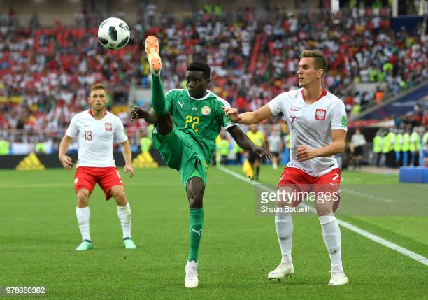 Moussa Wague of Senegal controls the ball under pressure from Arkadiusz Milik of Poland during the 2018 FIFA World Cup Russia group H match between...