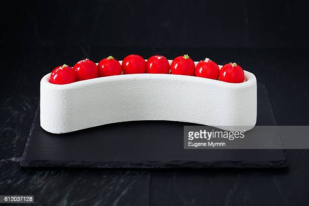 Mousse cake with red shiny decoration and white velvet spray