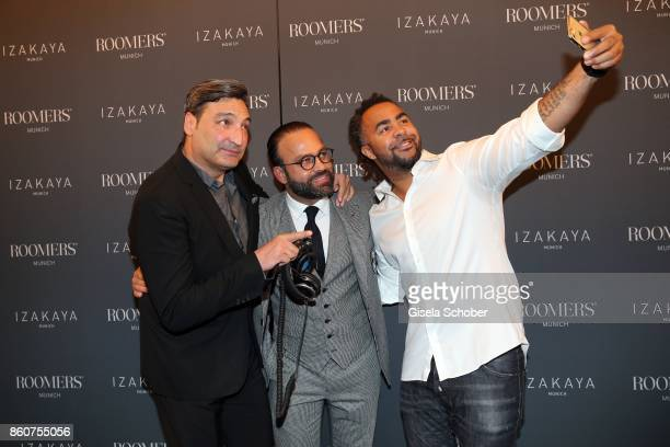 Mousse T Bardia Torabi General Manager Roomers Munich and Soccer player Patrick Owomoyela take a selfie during the grand opening of Roomers IZAKAYA...