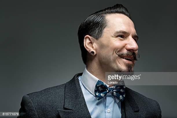 moustached classic man wearing a bow tie laughing