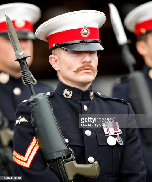 A moustachioed Royal Marine Commando forms part of an honour guard at The Royal Marines Commando Training Centre ahead of a visit by Prince Harry...
