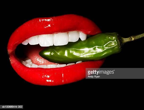 Mouth biting Jalepeno pepper, close-up, studio shot