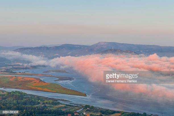 Mouth of the Miño river with clouds illuminated by the setting sun