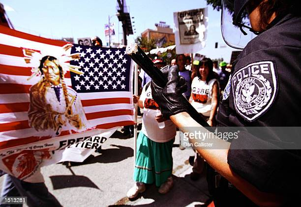 LAPD move in against demonstrators holding the american flag with an american indian imprinted on it during the Democratic National Convention August...