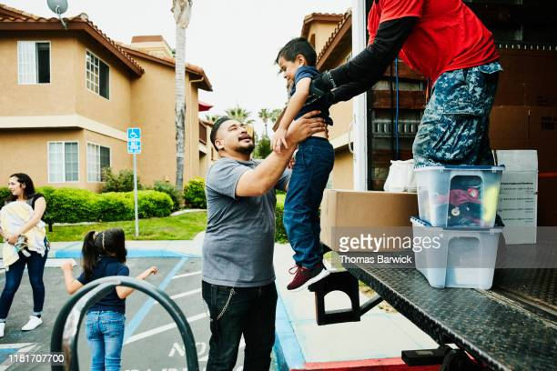 mover handing young boy to father from back of moving truck - funny customer service stock pictures, royalty-free photos & images